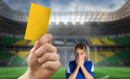 Hand holding up yellow card against football pitch in large stadium with fan photo
