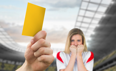 Hand holding up yellow card against football stadium with fan photo