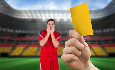 warning fans: Hand holding up yellow card against stadium full of germany football fans with player Stock Photo