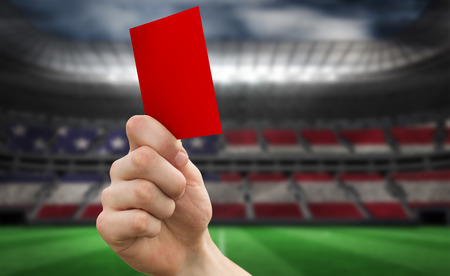 Hand holding up red card against stadium full of usa football fans photo