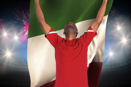 Excited handsome football fan cheering against fireworks exploding over football stadium and italy flag photo