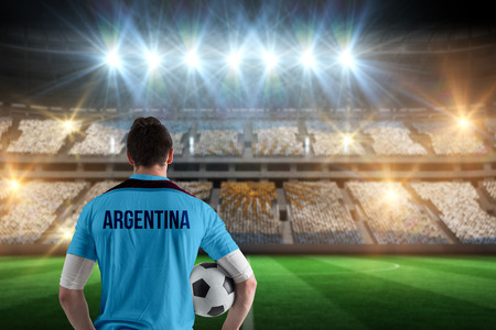 Argentina football player holding ball against stadium full of argentina football fans photo