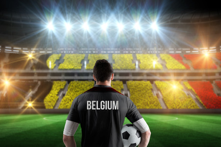 Belgium football player holding ball against stadium full of belgium football fans photo
