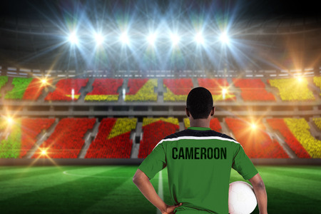 Cameroon football player holding ball against stadium full of cameroon football fans photo