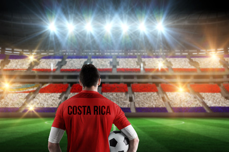Costa rica football player holding ball against stadium full of costa rica football fans photo