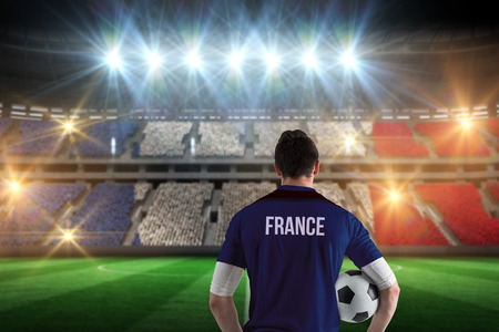 France football player holding ball against stadium full of france football fans photo
