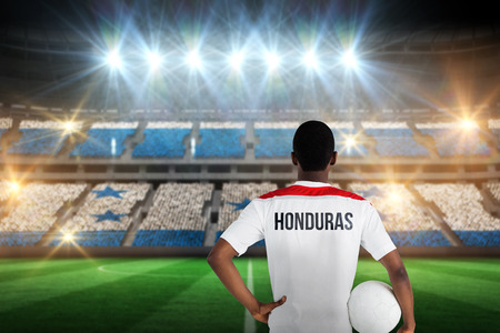 Honduras football player holding ball against stadium full of honduras football fans photo