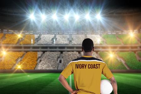 Ivory coast football player holding ball against stadium full of ivory coast football fans photo