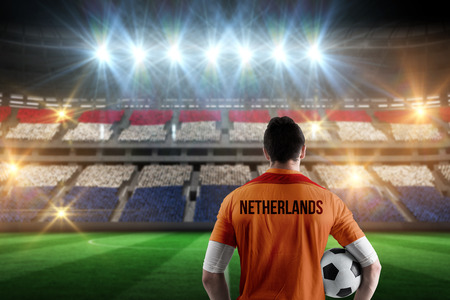 Netherlands football player holding ball against stadium full of netherlands football fans photo