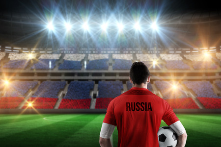 Russia football player holding ball against stadium full of russia football fans photo