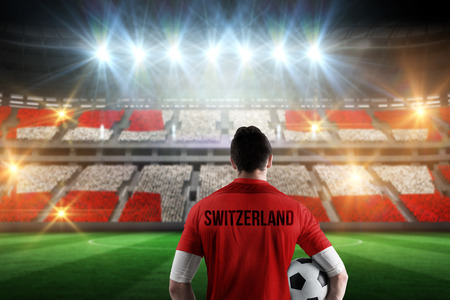 Swiss football player holding ball against stadium full of swiss football fans photo