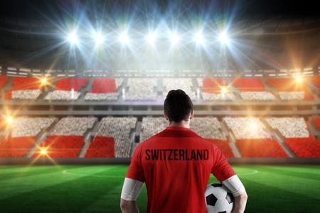 Swiss football player holding ball against stadium full of swiss football fans photo