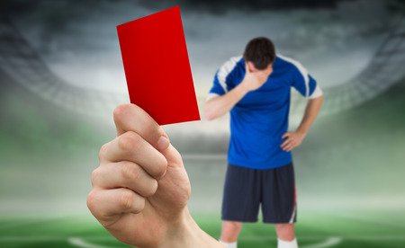 Composite image of hand holding up red card to player against football pitch in large stadium  photo