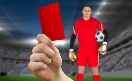 Composite image of hand holding up red card to goalie against football stadium photo