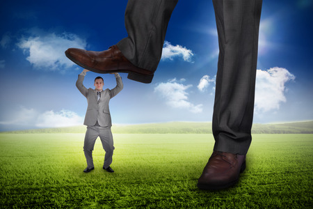 Composite image of businessman stepping on tiny businessman against sunny green landscape photo