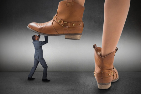 Composite image of cowboy boots stepping on businessman on grey background
