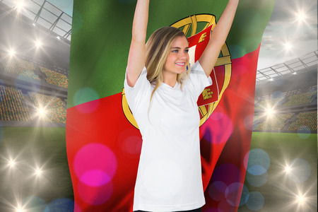 Pretty football fan in white cheering holding portugal flag against large football stadium with lights photo