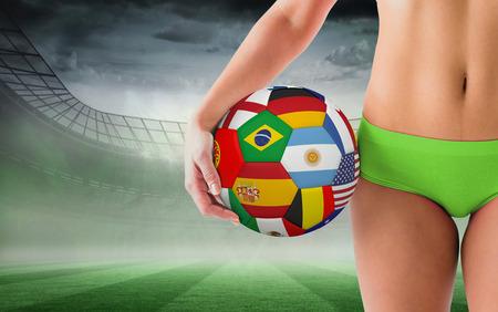 Fit girl in green bikini holding flag football against misty football stadium under spotlights photo