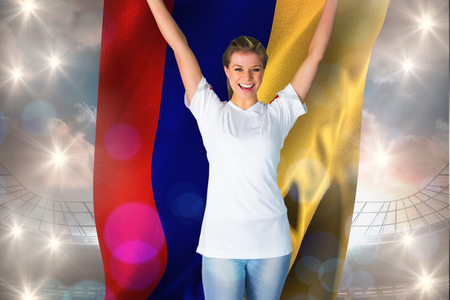 Pretty football fan in white cheering holding colombia flag against large football stadium under cloudy blue sky
