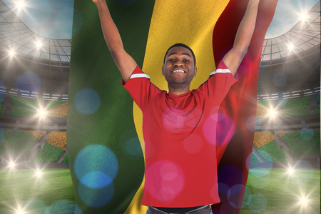 Excited handsome football fan cheering holding ghana flag against large football stadium with brasilian fans photo