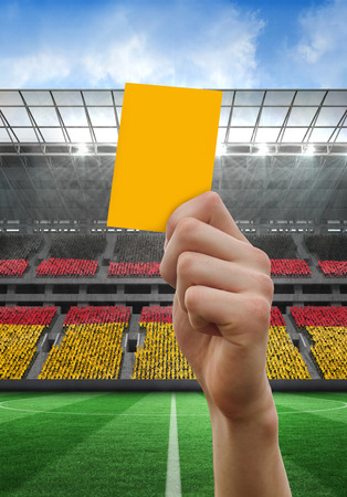 Hand holding up yellow card against stadium full of germany football fans photo