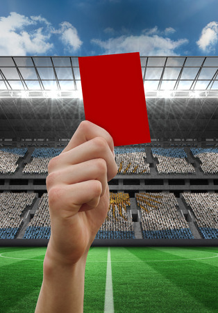 Hand holding up red card against stadium full of argentina football fans photo