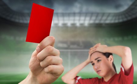 Hand holding up red card against football pitch in large stadium with fan photo
