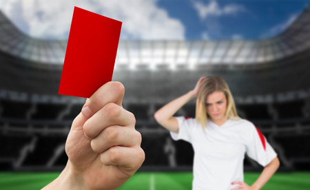 Hand holding up red card against large football stadium with empty stands with fan photo