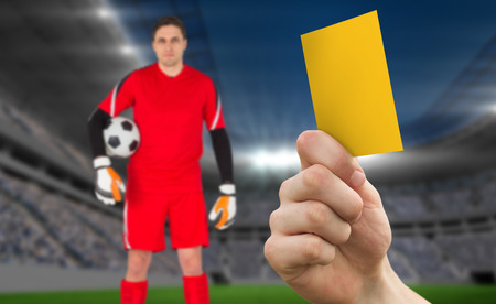Hand holding up yellow card against football stadium with goalie photo