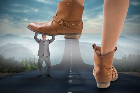 Composite image of cowboy boots stepping on businessman against road turning into arrow photo
