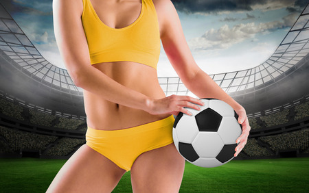 Fit girl in yellow bikini holding football against large football stadium with lights photo