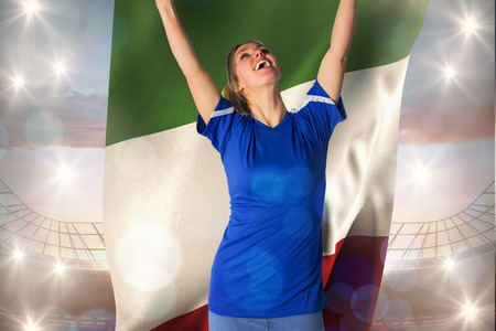 Cheering football fan in blue jersey holding italy flag against large football stadium under cloudy blue sky photo