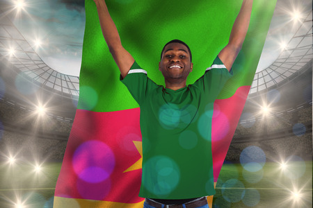 Cheering football fan in green jersey holding cameroon flag against large football stadium with lights photo
