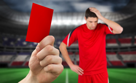 Hand holding up red card against stadium full of usa football fans with player photo