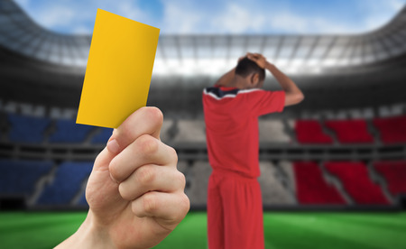 Hand holding up yellow card against stadium full of france football fans with player photo