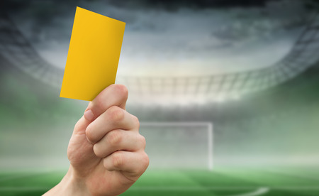 goalpost: Hand holding up yellow card against football pitch in large stadium