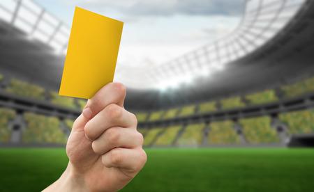 Hand holding up yellow card against football stadium photo