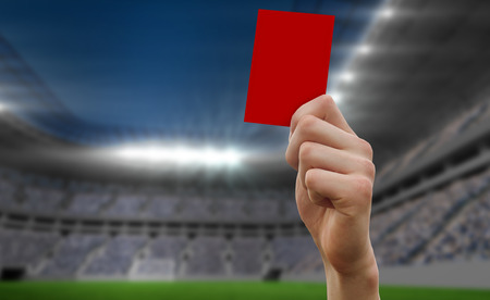 Hand holding up red card against football stadium photo