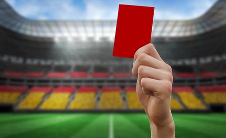 ドイツのフットボールのファンの完全スタジアムに対して赤のカードを持っている手