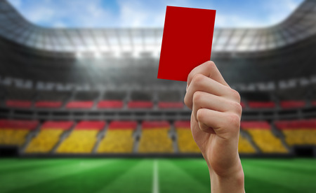 Hand holding up red card against stadium full of germany football fans Stock Photo