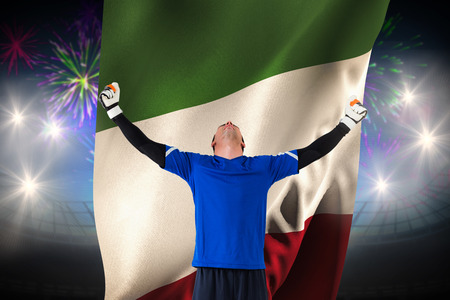 Goalkeeper celebrating a win against fireworks exploding over football stadium and italy flag photo