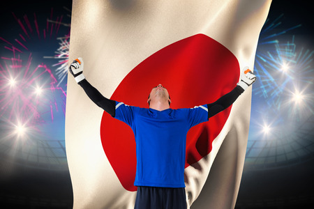 Goalkeeper celebrating a win against fireworks exploding over football stadium and japan flag photo