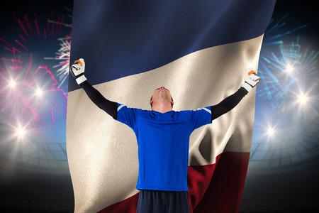 Goalkeeper celebrating a win against fireworks exploding over football stadium and france flag photo