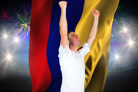 Cheering football fan in white against fireworks exploding over football stadium and colombia flag photo