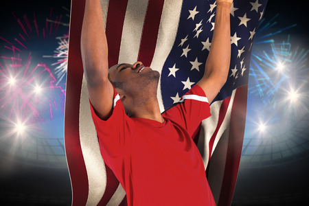 Excited handsome football fan cheering against fireworks exploding over football stadium and usa flag photo