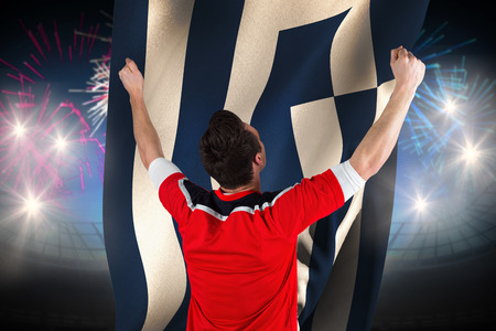 Excited football fan cheering against fireworks exploding over football stadium and greece flag photo
