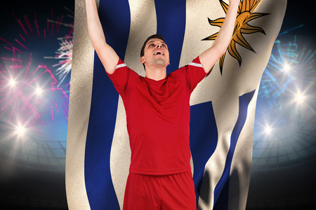 Excited football player cheering against fireworks exploding over football stadium and uruguay flag photo