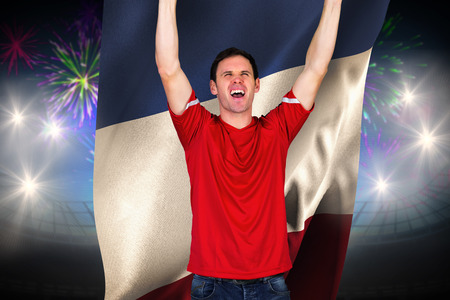 Cheering football fan in red against fireworks exploding over football stadium and france flag photo