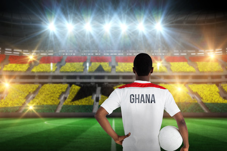 Ghana football player holding ball against stadium full of ghana football fans photo