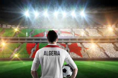 Algeria football player holding ball against stadium full of algeria football fans photo